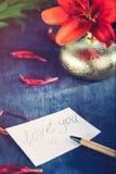 Je t'aime écrit sur une paix de paperr, de stylo et de vase d'or avec le lis et les pétales rouges sur le fond en bois foncé, ave Photos stock