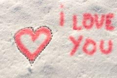 Je t'aime avec l'écriture de signe de coeur sur la neige Image stock