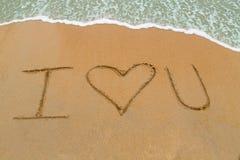 Je t'aime dessiné sur la plage sablonneuse avec l'approche de vague Photo libre de droits