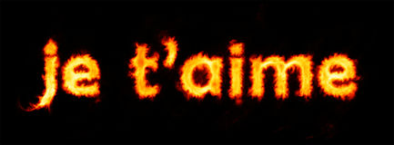 Je t`aime flaming inscription on black Stock Images