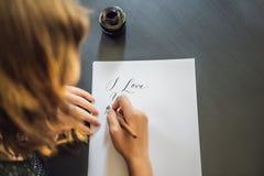 Je t'aime Le calligraphe Young Woman ?crit l'expression sur le livre blanc Inscrire les lettres d?cor?es ornementales calligraphi photo stock