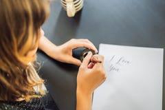 Je t'aime Le calligraphe Young Woman ?crit l'expression sur le livre blanc Inscrire les lettres d?cor?es ornementales calligraphi photos stock