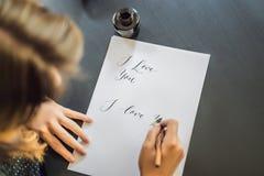 Je t'aime Le calligraphe Young Woman ?crit l'expression sur le livre blanc Inscrire les lettres d?cor?es ornementales calligraphi photographie stock libre de droits