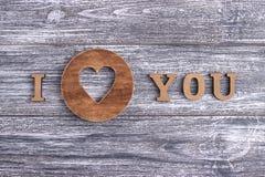Je t'aime, lettrage en bois, fond gris, Saint Valentin heureux de carte postale, configuration plate Image stock