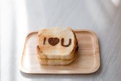 Je t'aime message dessus grillé sur la table en bois Photos stock