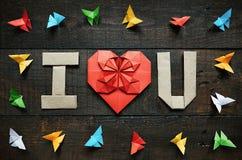 JE T'AIME, U a plié les lettres et le coeur rouge L'origami coloré empaquette le cadre de papillons sur le fond en bois âgé brun  images libres de droits