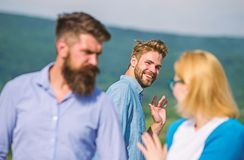 Jealous concept. Man with beard jealous aggressive because girlfriend interested in handsome passerby. Passerby smiling. To lady. Husband strictly watching his stock photography