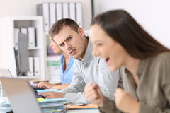 Jealous employee looking at a successful colleague. Portrait of a jealous employee looking at a successful colleague at office royalty free stock image