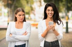 Free Jealous Girl Looking At Friend`s Phone Walking Together Outdoors Royalty Free Stock Photography - 184069877