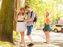 Jealous girl looking at flirting couple outdoor. Stock Photos
