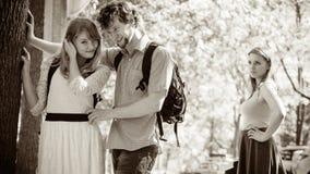 Jealous girl looking at flirting couple outdoor. Royalty Free Stock Photos
