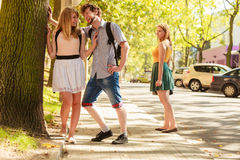 Jealous girl looking at flirting couple outdoor. Happy young women and men couple dating. Summer romance affair Royalty Free Stock Images
