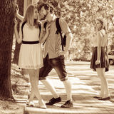 Jealous girl looking at flirting couple outdoor. Happy young women and men couple dating. Summer romance affair Stock Photography