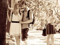 Jealous girl looking at flirting couple outdoor. Happy young women and men couple dating. Summer romance affair Royalty Free Stock Image