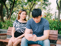 Jealous girlfriend peeking and spying her boyfriend mobile phone. While he is reading a message royalty free stock images
