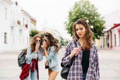 Jealous girls whispering about third girl in front of camera. royalty free stock photography