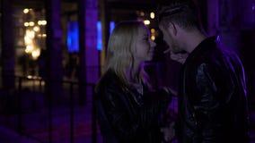 Jealous guy talking to girlfriend near night club, relationships, disagreement. Stock footage stock video