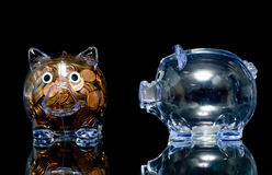 Jealous Pig. Two clear acryllic piggy banks one stuffed full of american pennies the other empty, Illustration of the haves and the have nots.  one pig is Royalty Free Stock Photography