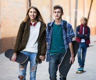 Jealous teen and his friends after conflict. Jealous teen and his smiling european friends after conflict outdoors Royalty Free Stock Photography