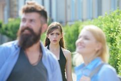 She is jealous. Unhappy girl feeling jealous. Bearded man cheating his girlfriend with another woman. Jealous woman look. She is jealous. Unhappy girl feeling royalty free stock photo