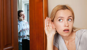 Jealous wife, overhearing her husband Royalty Free Stock Photos