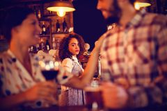 Jealous woman looking at couple flirting with each other. Jealous women looking at couple flirting with each other in pub stock image