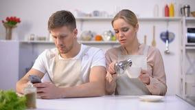 Jealous woman peeping in husbands smartphone, relationship crisis, distrust. Stock footage stock video