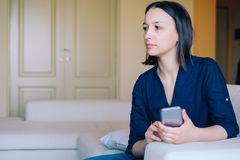 Jealous woman portrait watching one phone message. Worried doubtful woman holding smartphone royalty free stock photos