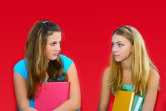 Jealousy. Two teenage girls holding books, jealous expressions on their faces Stock Photography