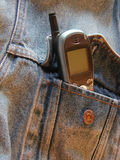 Jean jacket with cell phone. Cell phone sticking out of denim jacket pocket stock photo