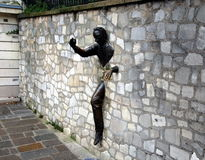Jean Marais sculpture Le Passe-Muraille. PARIS, FRANCE - DEC 28, 2011 - Jean Marais sculpture Le Passe-Muraille (Man Who Walked through Walls, 1989) on Royalty Free Stock Photo