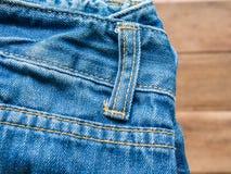 Jean på wood bakgrund Arkivbild