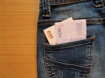 Jean pocket and money. On wood back ground Royalty Free Stock Photo