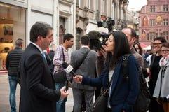 Jean Rottner som borgmästaren av Mulhouse intervjuade vid television på öppningen av Starbucks i Mulhouse Arkivbilder