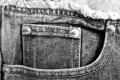Closeup of black denim jean pockets. Black and white denim jean pockets with studs or rivets and worn edges royalty free stock photo