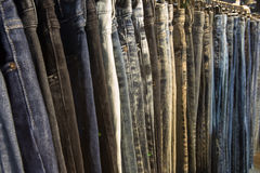 Jean. Selective focus row of hanged blue jeans in a shop stock photography