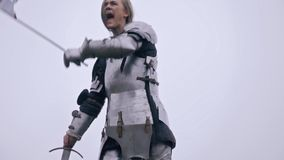 A woman warlord calls her army and waving a flag, slow motion. Jeanne d`Arc in medieval armor gives the signal to the army stock footage