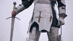 Wounded Woman knight holding a bloodied sword, slow motion. Jeanne D`Arc in medieval armor holds a wounded hand with a sword stock video footage