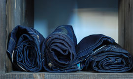 Jeans. Rolled blue jeans on the shelf Stock Photography
