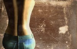 Jeans 3. Bare-backed woman in jeans sitting against a grunge background Stock Images