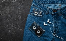 Jeans, audio cassette, headphones layout on a black concrete table. Conceptual photo Stock Photos