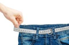 Jeans avec la bande de mesure d'isolement sur le blanc Photos stock