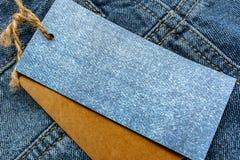 Jeans avec le prix à payer de papier blanc Photographie stock libre de droits