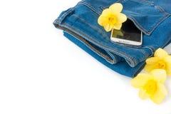 Jeans avec le téléphone portable et les fleurs sur le fond blanc Photo libre de droits