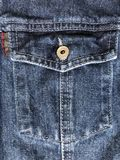 Jeans background with buttoned chest pocket. Blue denim with decorative stitching on the pocket stock image