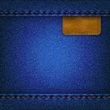 Jeans background with a leather label. Blue jeans background with leather label sewn Stock Image