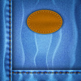 Jeans background with a leather label Royalty Free Stock Images