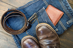 Jeans, belt , shoes and wallet on wooden background Royalty Free Stock Photography