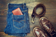 Jeans, belt , shoes and wallet on wooden background Royalty Free Stock Photos