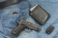 Jeans, Black Leather Bi-Fold Wallet, Handgun and a car key Royalty Free Stock Photos